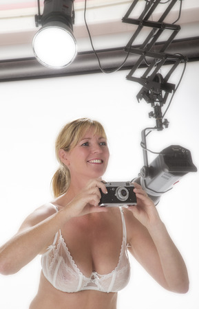 Woman taking picture in a photo studio with an old film camera