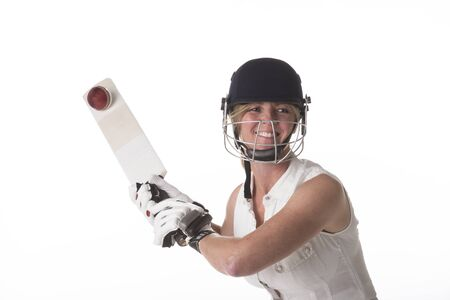 hitting: Woman hitting cricket ball with a bat