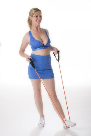 muscle toning: Woman in fitness training using an exercise resistance band to tone muscles