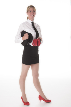 Mini skirt: A uniformed chauffeuse standing in a mini skirt holding driving gloves Stock Photo