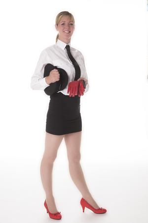 mini falda: Un chauffeuse uniformado de pie en una mini falda que sostiene guantes de conducci�n