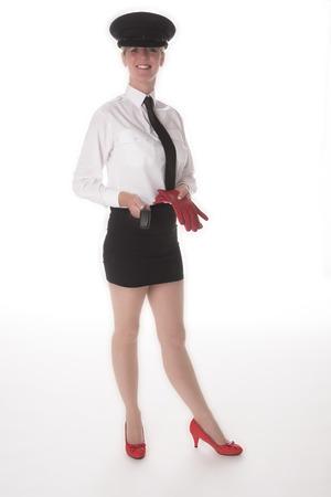 mini skirt: Une chauffeuse en uniforme debout dans une mini jupe tenant gants de conduite Banque d'images