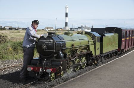 loco: Engine driver polishing the Green Goddess loco which operates a passenger service between Hythe and Dungeness in Kent UK
