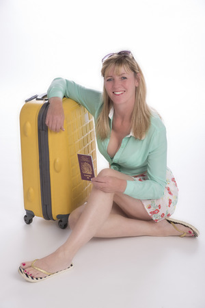 holidaymaker: Woman holidaymaker with passport and suitcase