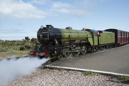 narrow gauge railroad: A vintage steam locomotive on a narrow guage track Editorial