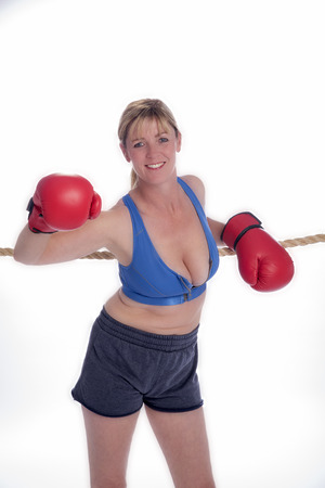 female boxer: Female boxer leaning on the ropes of a boxing ring