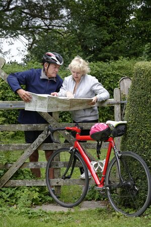 togther: Elderly couple map reading during a cycle ride in the countryside