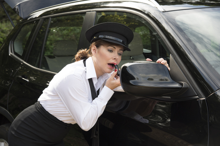 'getting ready': Getting ready for driving a woman chauffeur applying makeup Stock Photo