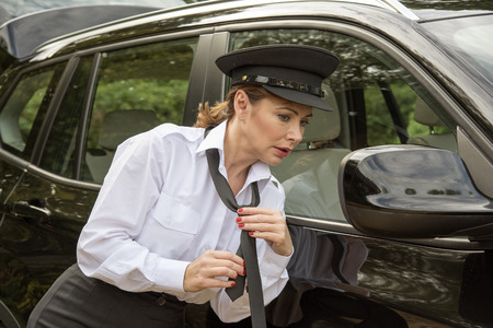 driver cap: Attractive woman chauffeur tying her uniform tie in the wing mirror of her car