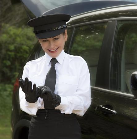 Frau Fahrer, die sich ihre einheitliche schwarze Lederhandschuhe Standard-Bild - 45443861