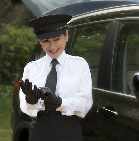Woman chauffeur putting on her uniform black leather gloves Imagens - 45443861