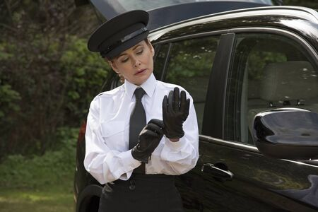 leather gloves: Woman chauffeur putting on her uniform black leather gloves