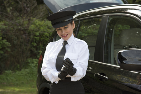 putting on: Woman chauffeur putting on her uniform black leather gloves