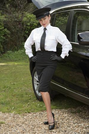 alongside: Woman chauffeur in uniform standing alongside her car