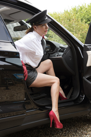 exits: Professional woman driver showing long legs as she exits the car Stock Photo