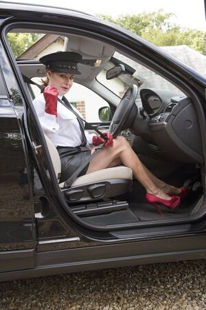 Professional woman driver showing long legs as she fastens seatbelt Stock Photo