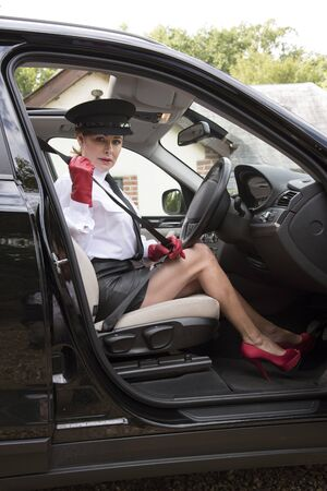 fastens: Professional woman driver showing long legs as she fastens seatbelt Stock Photo