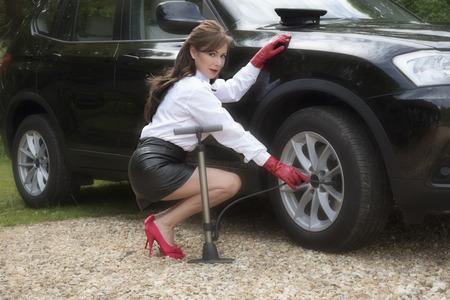 mini skirt: Mujer chófer control de presión de los neumáticos y infla el neumático Foto de archivo