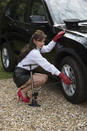 falda corta: Mujer chófer control de presión de los neumáticos y infla el neumático Foto de archivo