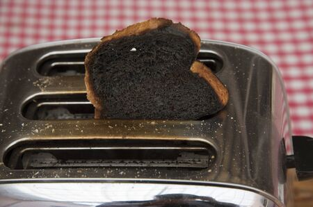 burnt toast: Slice of burnt toast in a toaster machine