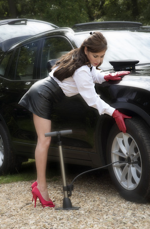 inflating: Woman chauffeur checking tyre pressure and inflating tire Stock Photo