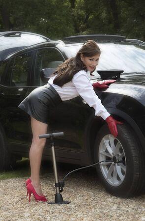 minifalda: Mujer chófer control de presión de los neumáticos y infla el neumático Foto de archivo