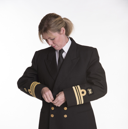 servicewoman: Female naval officer in getting dressed into uniform jacket