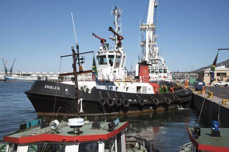 berth: Ocean going tug Enseleni leaving her berth in Cape Town harbour South Africa