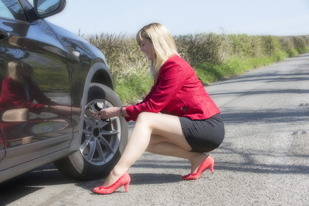 motorist: Motorist with long legs and a short skirt performing a tyre pressure check on her car Stock Photo