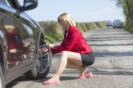 short skirt: Motorist with long legs and a short skirt performing a tyre pressure check on her car Stock Photo