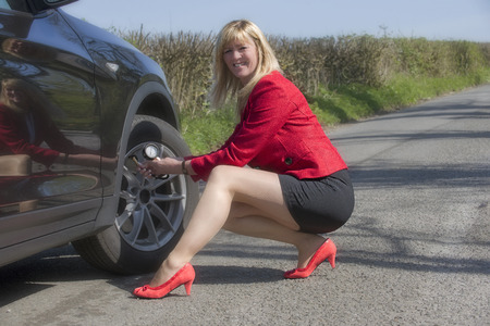 Motorist with long legs and a short skirt performing a tyre pressure check on her car Stock Photo