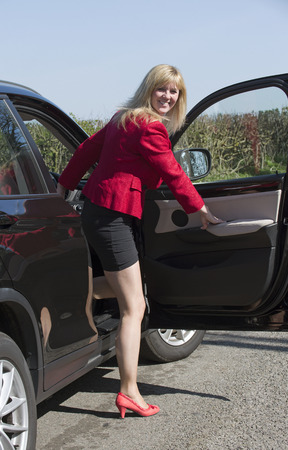 Woman driver getting into and out of her car Stock Photo