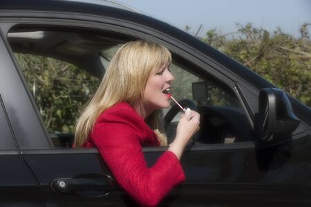gloss: Motorist applying lip gloss using a driving mirror