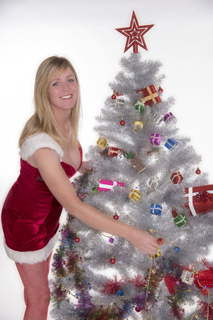 decorating christmas tree: Woman in Santa costume decorating a Christmas tree Stock Photo