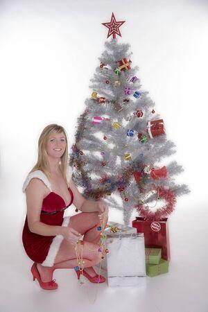 decorating christmas tree: Woman in Santa costume decorating a Christmas tree Stock Photo