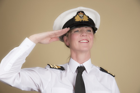 Female navy officer in uniform of a Lt Commander saluting