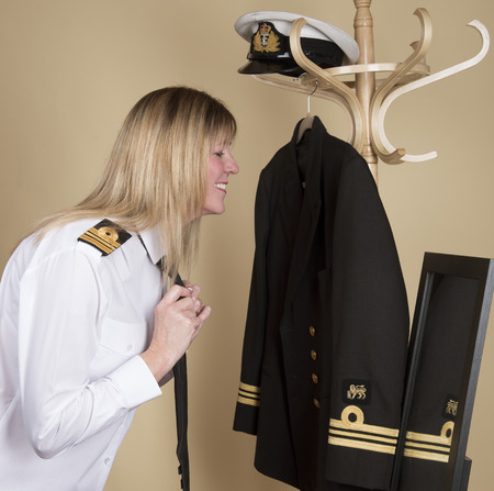 commander: Female naval Lt Commander getting ready for duty Tying her black uniform tie Stock Photo