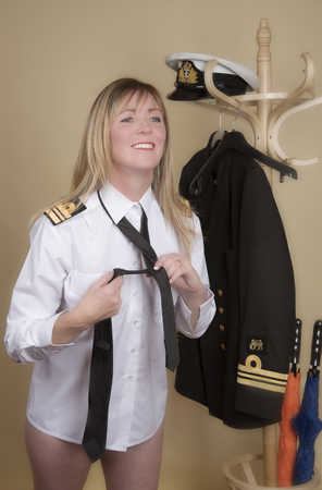 lt: Female naval Lt Commander getting ready for duty Tying her black uniform tie Stock Photo