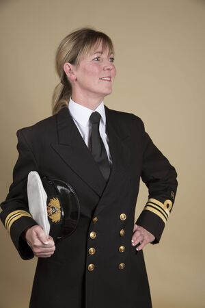 Portrait of a woman Lt Commander in uniform and holding her hat under her arm