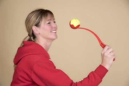 flick: Womans hand holding a tennis ball launcher used for throwing ball for a dog Stock Photo