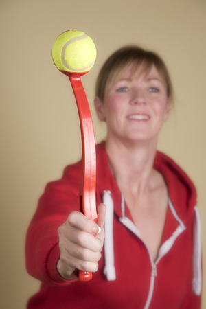 womans: Womans hand holding a tennis ball launcher used for throwing ball for a dog Stock Photo