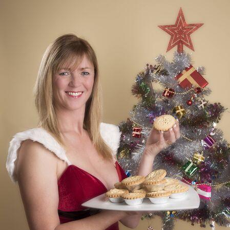 carne picada: Mujer en traje de Santa sosteniendo un plato de pasteles de carne tradicionales