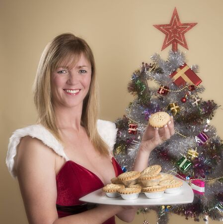 Woman in Santa costume holding a plate of traditional mince pies Stock Photo