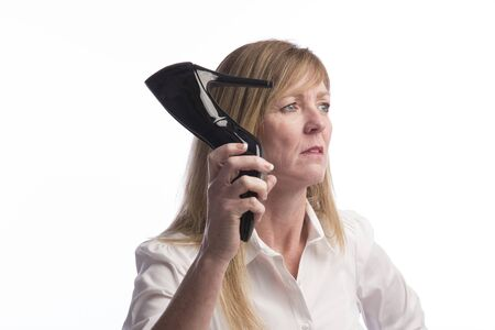 outrage: Woman holding a stiletto shoe in extreme anger