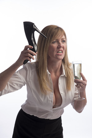 displeasure: Woman holding a stiletto shoe in extreme anger