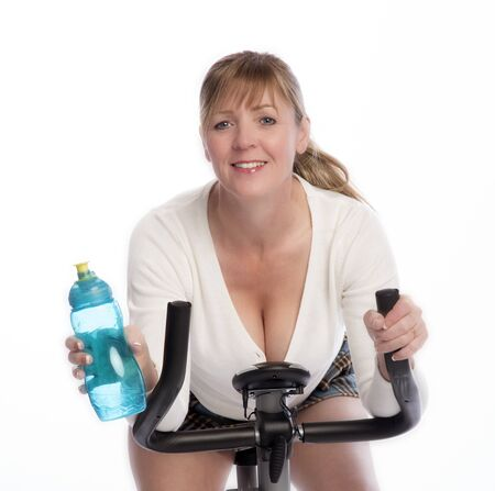 age forty: Woman working out on an exercise bike taking a drink of water from a plastic bottle