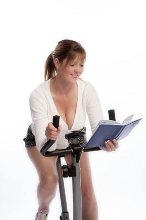 age forty: Woman working out on an exercise bike and reading a book