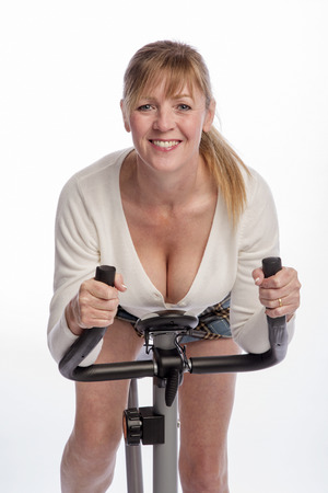 age forty: Portrait of a woman riding an exercise bike Stock Photo