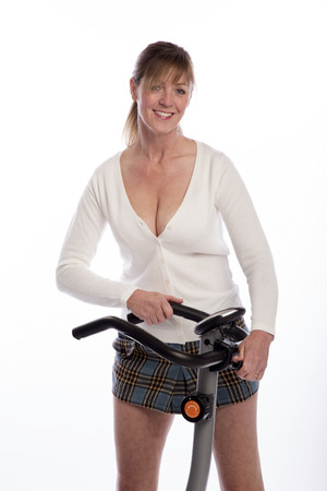 age forty: Woman adjusting the handlebars of an exercise bike Stock Photo