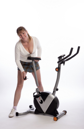 age forty: Woman adjusting the height of the saddle on an exercise bike Stock Photo